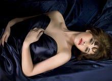 Mulher que encontra-se na obscuridade - seda azul Fotos de Stock Royalty Free