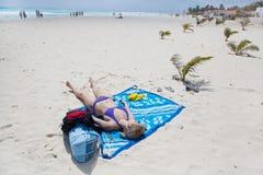 Mulher que encontra-se na praia Imagens de Stock Royalty Free