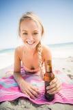 Mulher que encontra-se na praia com garrafa de cerveja Foto de Stock Royalty Free