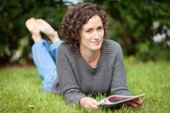 Mulher que encontra-se na terra Tem um sorriso encantador barefoot imagem de stock royalty free