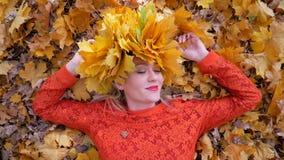 Mulher que encontra-se nas folhas de outono video estoque