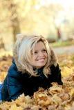 Mulher que encontra-se nas folhas de outono Fotografia de Stock