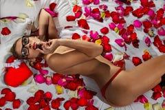 Mulher que encontra-se nas pétalas da flor Fotografia de Stock Royalty Free