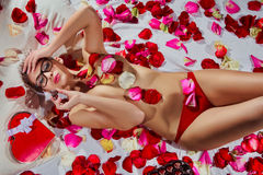Mulher que encontra-se nas pétalas da flor Imagens de Stock Royalty Free