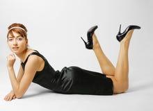 Mulher que encontra-se nas sapatas pretas colocadas saltos Imagens de Stock Royalty Free
