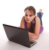 Mulher que encontra-se no assoalho com portátil Imagens de Stock