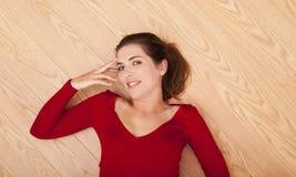 Mulher que encontra-se no assoalho e no sorriso Fotos de Stock Royalty Free