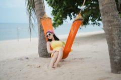 Mulher que encontra-se no berço na praia fotografia de stock