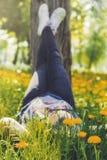 A mulher que encontra-se no campo de grama encheu-se com as flores amarelas Imagem de Stock
