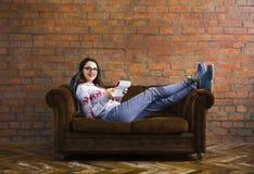 Mulher que encontra-se no sofá com PC da tabuleta Imagem de Stock