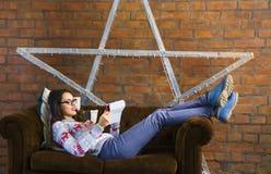 Mulher que encontra-se no sofá com PC da tabuleta Fotos de Stock Royalty Free