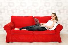 Mulher que encontra-se no sofá com portátil Imagem de Stock