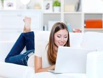 Mulher que encontra-se no sofá com portátil Fotografia de Stock Royalty Free