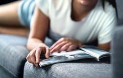 Mulher que encontra-se no sofá e que lê um compartimento da forma ou da beleza Senhora que aprecia seu dia livre com notícia do e foto de stock royalty free