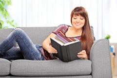 Mulher que encontra-se no sofá e que lê uma novela em casa foto de stock royalty free