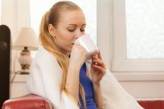 Mulher que encontra-se no sofá sob o chá bebendo da cobertura Foto de Stock Royalty Free