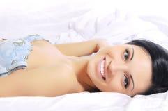 Mulher que encontra-se no sorriso da cama Imagens de Stock Royalty Free