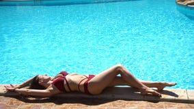 Mulher que encontra-se perto da piscina do verão vídeos de arquivo