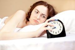 Mulher que encontra-se uma cama com alarme (foco no alarme) Foto de Stock