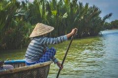 mulher que enfileira um barco da cesta, ao longo da floresta da água do coco, em Hoi An fotos de stock royalty free
