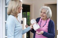 Mulher que entrega o jornal ao vizinho idoso imagem de stock royalty free