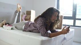 Mulher que envia a mensagem de texto que move-se na casa nova video estoque