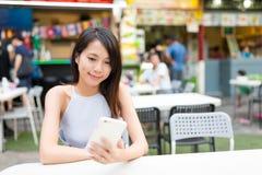 Mulher que envia sms no telefone celular no restaurante exterior fotografia de stock