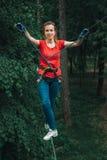 Mulher que equilibra na elevação no parque da corda da aventura da floresta imagem de stock royalty free