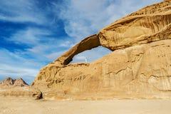 Mulher que escala à ponte da rocha de Burdah no deserto de Wadi Rum fotografia de stock