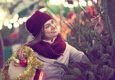 Mulher que escolhe a árvore do ` s do ano novo na feira Fotos de Stock Royalty Free