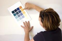 Mulher que escolhe a cor da pintura para a parede Fotografia de Stock Royalty Free