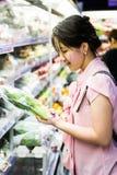 Mulher que escolhe a couve chinesa Foto de Stock
