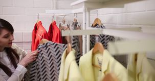 Mulher que escolhe e que compra a roupa à moda na loja de roupa ou no boutique do fato Comprar fêmea dos clientes na moda video estoque