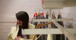 Mulher que escolhe e que compra a roupa à moda na loja de roupa ou no boutique do fato Comprar fêmea dos clientes na moda vídeos de arquivo