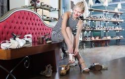 Mulher que escolhe em pares de sapatas na loja da forma Imagens de Stock Royalty Free