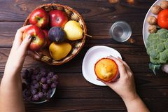 Mulher que escolhe entre a comida lixo e os frutos fotografia de stock