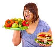 Mulher que escolhe entre a fruta e o Hamburger Foto de Stock