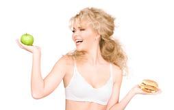 Mulher que escolhe entre o hamburguer e a maçã Imagem de Stock Royalty Free