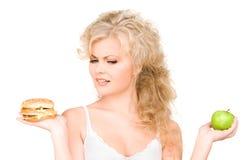 Mulher que escolhe entre o hamburguer e a maçã Imagens de Stock Royalty Free