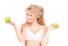 Mulher que escolhe entre o hamburguer e a maçã Fotos de Stock