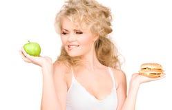 Mulher que escolhe entre o hamburguer e a maçã Fotografia de Stock Royalty Free