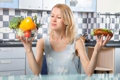 Mulher que escolhe entre vegetais e sanduíche Imagem de Stock