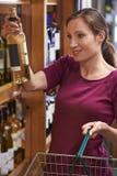 Mulher que escolhe a garrafa do vinho branco da prateleira no supermercado imagens de stock