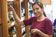 Mulher que escolhe a garrafa do vinho branco no supermercado fotografia de stock royalty free