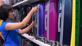 Mulher que escolhe malas de viagem na loja vídeos de arquivo