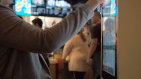 Mulher que escolhe o alimento através da máquina do autosserviço no restaurante do fast food Menina que usa o terminal do toque d vídeos de arquivo
