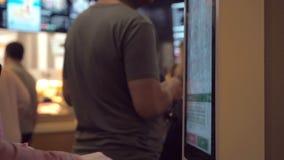 Mulher que escolhe o alimento através da máquina do autosserviço no restaurante do fast food Menina que usa o terminal do toque d filme