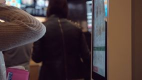 Mulher que escolhe o alimento através da máquina do autosserviço no restaurante do fast food Menina que usa o terminal do toque d video estoque