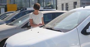 Mulher que escolhe o carro para comprar no negócio que deseja realmente video estoque