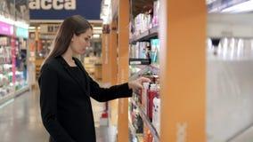 Mulher que escolhe o detergente para a roupa na mercearia Mulher de negócios no supermercado Imagens de Stock